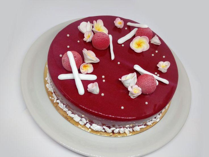 Glassa a specchio rosso bordeaux, che racchiude una mousse leggera al cioccolato fondente, gelatina tropicale e sponge cake alla vaniglia.