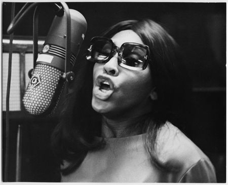 1961: EXCLUSIVE Headshot of vocalist Tina Turner singing into a microphone during a recording session in a dimly-lit studio, Los Angeles, California.
