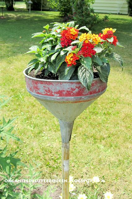 Funnel planter on a stick now in bloom with red lantana.