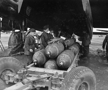 "Preparing to load 1,000-lb MC bombs into the bomb-bay of an Avro Lancaster B Mark III of No. 106 Squadron RAF at RAF Metheringham, prior to a major night raid on Frankfurt. The stencilled lettering around the circumference of each bomb reads ""RDX/TNT"""