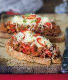 Ďábelské topinky 2 lžc olivového oleje     1 cibule, nakrájená nadrobno     2 červené chilli papričky, zbavené semen, nakrájené na proužky     1 červená paprika, nakrájená na proužky     300 g mletého hovězího masa     100 g rajského protlaku     400 g hotové rajčatové omáčky na těstoviny (např. od Panzani Napoletana nebo Primavera)     mořská sůl, případně cukr na dochucení     200 g ementálu nebo jiného tvrdého sýra, nastrouhaného     5 stroužků česneku