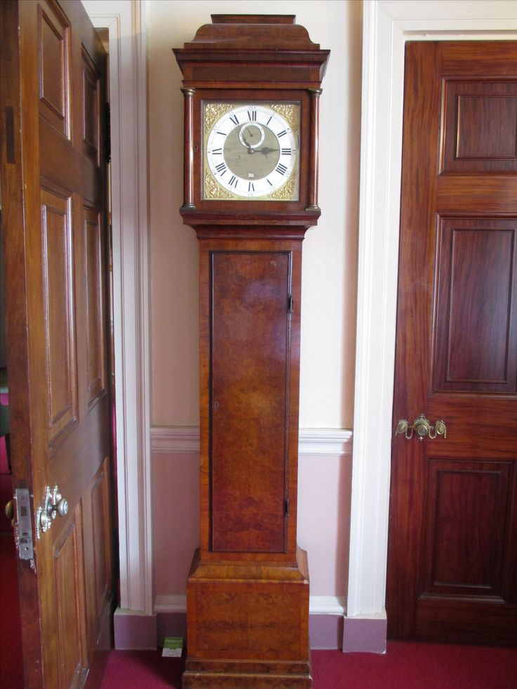 Walnut longcase clock with 12 inch dial.  Incribed, 'George Graham, London' (b.1673, d. 1751).  Case has the trade label 'Wall and Son, Richmond, Surrey'.  Bolt and shutter maintaining clock power during winding process.  Deadbead escapement with calibrated rating nut for pendulum.  Blue steel hands.  Silvered chapter ring for legibility, 8 day movement.  Ante-room to the Blue Drawing Room.