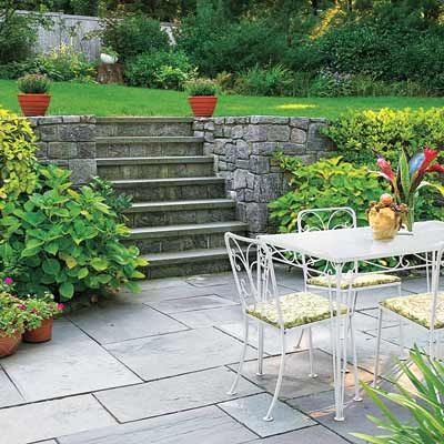 The rough stones in a retaining wall contrast nicely with the smooth bluestone on this sunken patio. Adding even more interest are the various sizes of pavers and the mix of colors, including shades of blue, gray, and purple. The patio's joints fit so tightly that the surface is smooth enough to roll out a charcoal kettle for barbecues.     Learn how to install a cut bluestone patio.