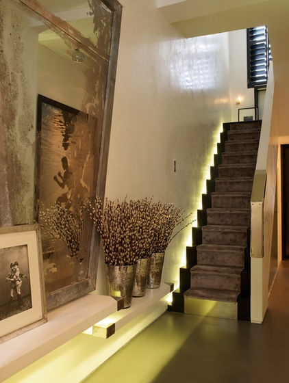 AMBIENT (Now this is truly opulent furnishing ! - Ambient lighting coming up from behind the walls complements the townhouse's natural light. Silk carpet runners line the stairs and set a dramatic tone in the entry. Mirror: B & T Antiques; flowers, vases: John Carter Flowers)