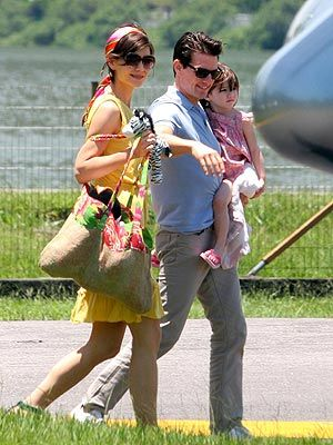 Celebrity travel necessities: Large tote bag, headscarf, shades, Tom Cruise & baby Suri.