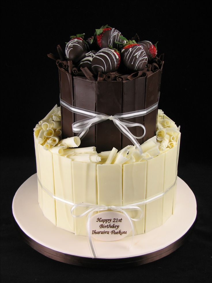 This is a chocolate mudcake with dark chocolate panels and a red velvet cake covered in white chocolate panels. The cake is decorated with chocolate coated strawberries and chocolate curls.