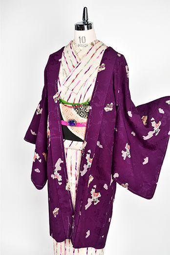 打ち出の小槌や隠れ笠、分銅や七宝など寿ぎの心をこめた宝尽くしの地紋浮かぶ深みのある紫の地に、舶来の色絵の陶磁器の欠片を散りばめたような装飾模様が染め出されたアンティークの羽織です。