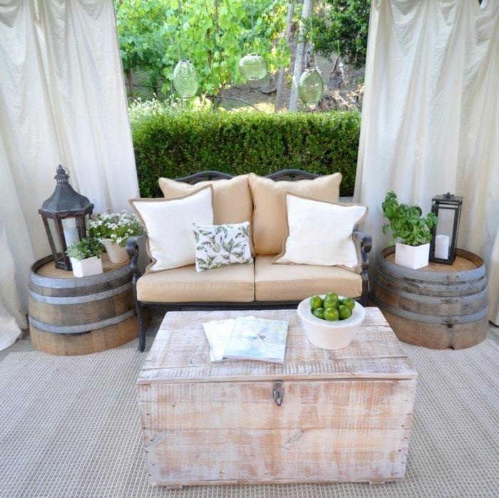petit canapé avec coussins, lanternes, fleurs blanches et coffre en bois sur la terrasse