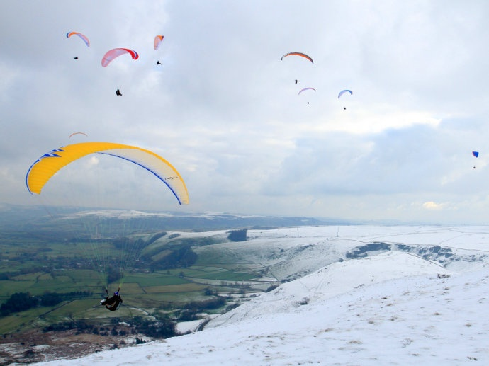 Paragliders take to the chilly skies over Mam Tor, high above Caslteton in the Derbyshire Peak District. Cold easterly winds made for perfect flying conditions
