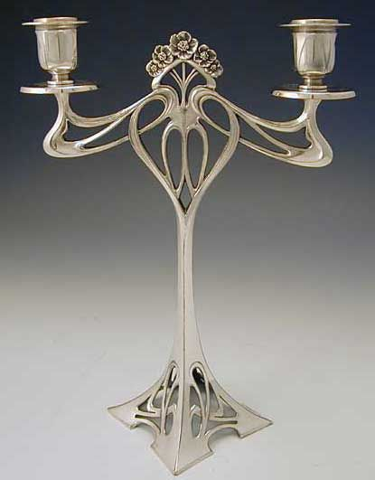 Manufacturer 	WMF  Description 	Pair of polished pewter twin-branched candlesticks with Art Nouveau floral decoration  Country of Manufacture 	Germany  Date 	Circa 1906