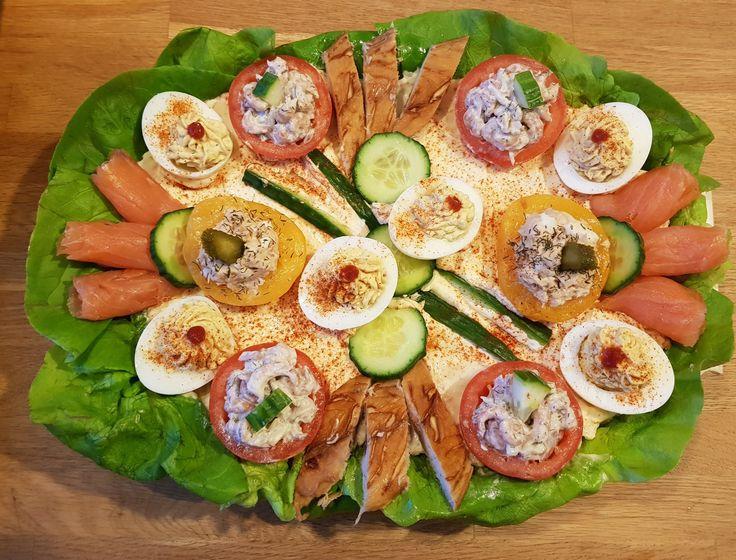 Koude schotel met vis. Opgemaakt met perziken gevuld met tonijnsalade, gevulde eitjes, tomaatjes gevuld met Hollandse garnalen, gerookte zalm en gerookte makreelfilet.