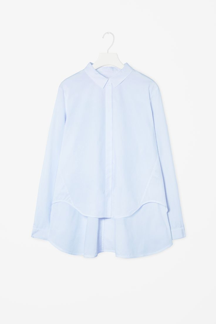 A-line poplin shirt | Made from stretch cotton poplin, this shirt is a wide A-line shape with draped sides and a modern graduated hemline. Long-sleeved, it has a small collar, cut-out hemline and hidden front buttons. | €59