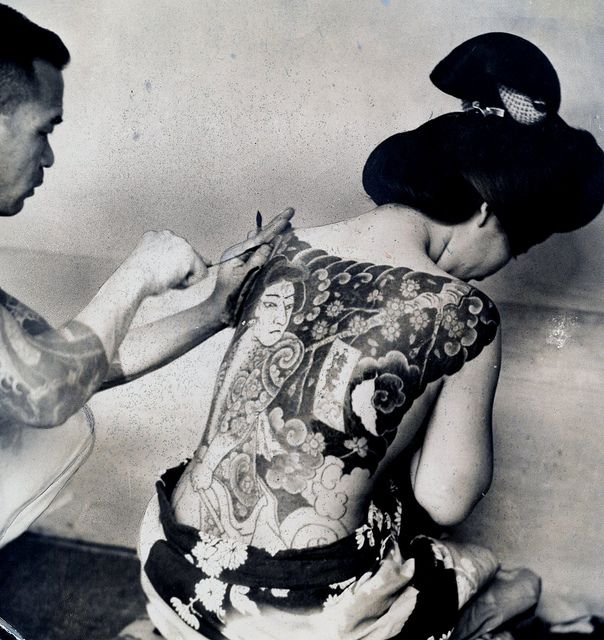 """This is a Press photo from 1937 that has been trimmed down from a larger photograph sometime during its life. On the back is typed the following: """"Tattoo / Tattooing. Because they believe that tattooing makes them beautiful many Japanese women endure the painful process without an opiate. They spend hundreds of dollars in this manner. Roto 9/26/37."""""""