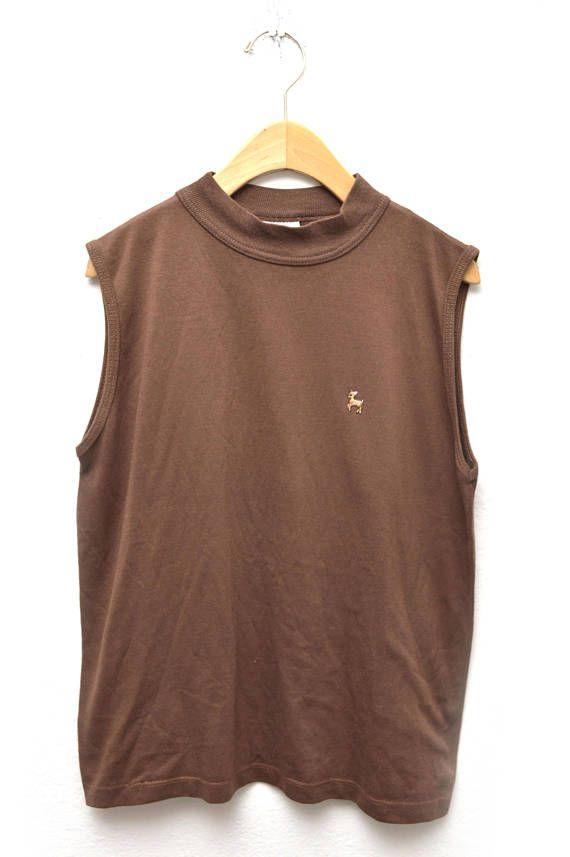 Esta camiseta vintage básica ha sido adornada con un pequeño hierro-en remiendo que complementa el color de la camisa.  Para mejores resultados, lavar con agua fría y no seque a fuego alto para que no se disminuya la adherencia.  Marca: Simplemente lo básico Tamaño: grande Material: Algodón, poliester  Medidas: Pecho: 39 Longitud: 23