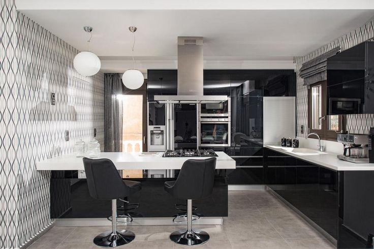 Μοντέρνα κουζίνα με πορτάκια από μαύρο γυαλιστερό ακρυλικό και ενσωματωμένες χούφτες αλουμινίου.