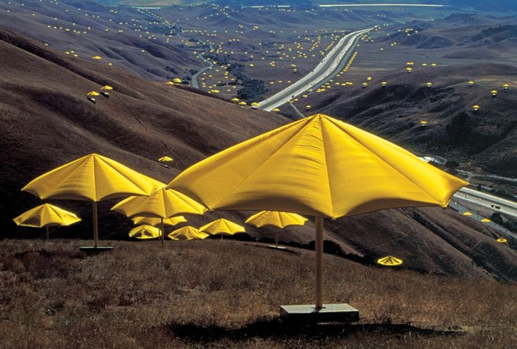 field dotted with yellow umbrellas by Christo and Jeanne-Claude