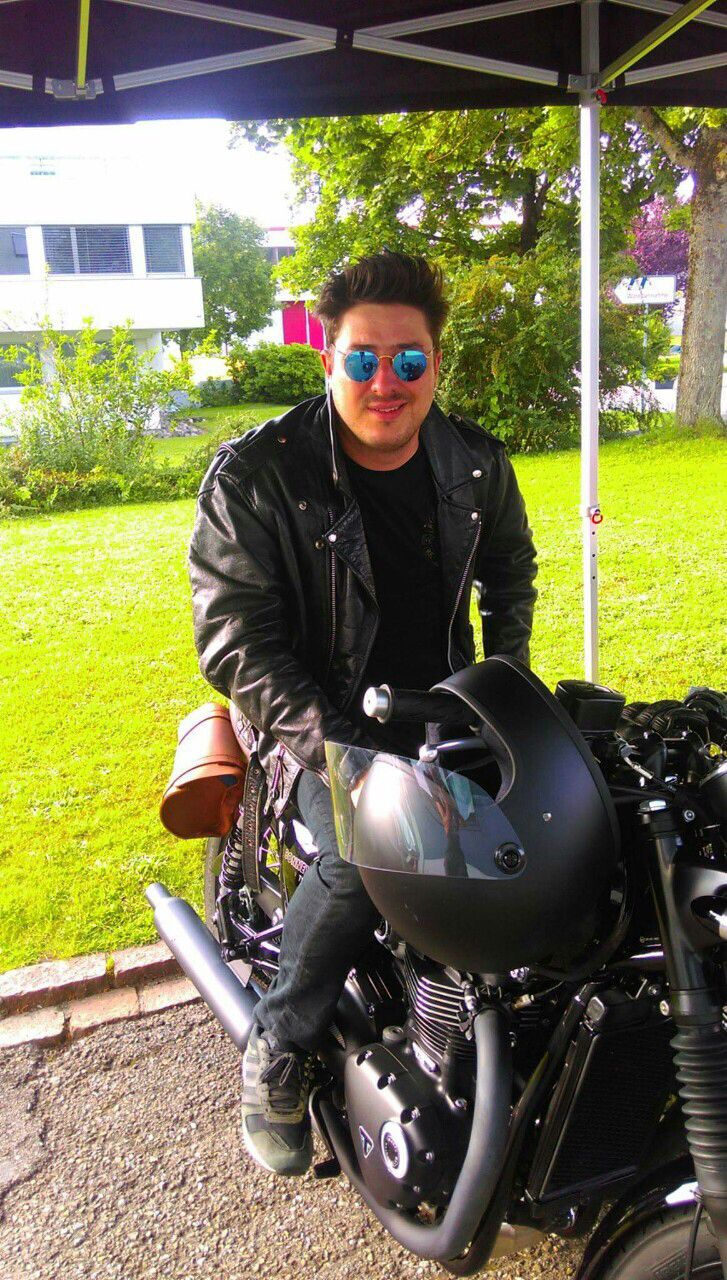 Marcus Mumford on his Triumph motorcycle. That hair though