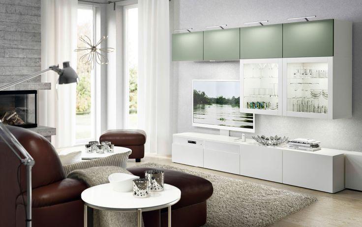 Dnevna soba s bijelom TV klupom s bijelim ladicama i zidnim elementima u kombinaciji svijetlo zelenih vrata i bijelih vrata s pločama od kaljenog stakla. Prikazan je i tamno smeđi kožni dvosjed s počivaljkom i podnožnik.