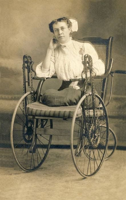 Dama de 1900 con amputación de ambas piernas, utilizando una silla con un sistema de cadenas de transmisión de bicicleta y manivelas, que la permitía desplazarse sin ayuda de un asistente.  La mayoría de las sillas de ruedas manuales son accionados por el usuario haciendo girar las ruedas directamente. Esta silla, por el contrario, era accionada a través de cadenas por dos manivelas de mano a cada lado.