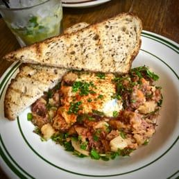 Photo of The Kirkland Tap & Trotter - Somerville, MA, United States. SUNDAY BRUNCH: Corn beef hash with a soft poached egg, hollandaise & a frosty lemony cocktail #kttfeed