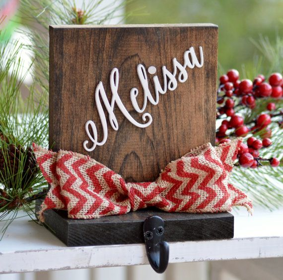 Personalized Stocking Holder, Wood Stocking Holder For Mantle Top, Rustic Christmas Decor, Stocking Label, Stocking Hanger, Stocking Hook  DESCRIPTION: This rustic stocking holder makes a beautiful holiday accent to your mantle! Theyre made from solid wood and stained a dark brown. Each is then personalize with your choice of names cut from separate wood to give them a 3-D effect, and adorned with a rustic burlap bow in your choice of colors!  SIZE: Each is 7 x 5.5 inches.  INCLUDED: This…