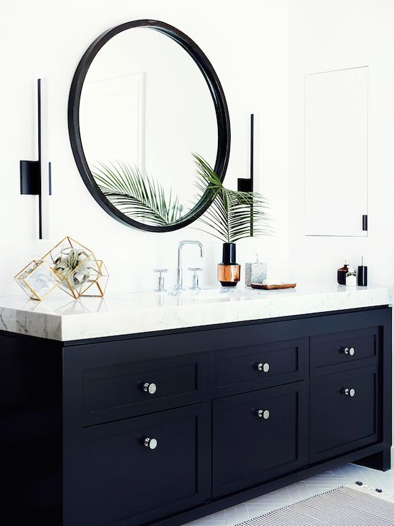 Black and white bathroom centers on a chic vanity painted Farrow and Ball Pitch Black adorned with round nickel pulls alongside a polished Statuarietto Marble counter which frames a single sink and modern faucet below a black round vanity mirror flanked by modern black and white wall sconces with a hidden medicine cabinet to the right.