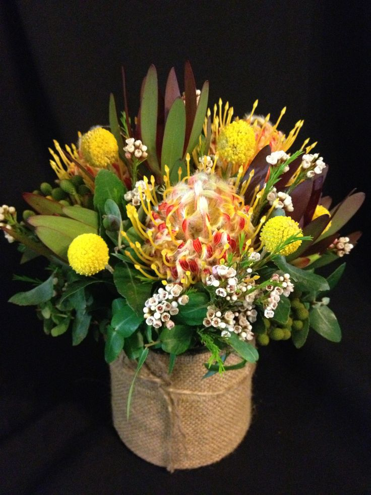 table centre arrangements with leucadendron billy buttons leucospernum and geraldton wax flower & blue gum