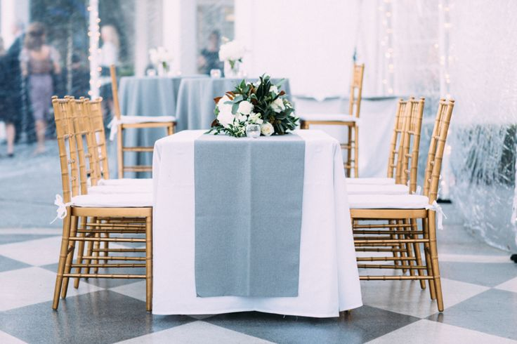 Elegant gold-toned chairs and dusty blue table decor: http://www.stylemepretty.com/florida-weddings/tampa/2015/08/14/elegant-black-tie-tampa-yacht-club-wedding/ | Photography: Kallima Photography - http://www.kallimaphotography.com/