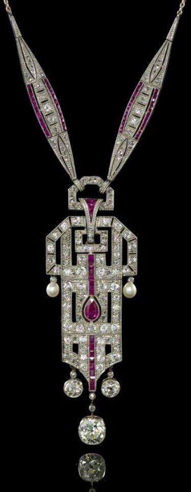 An Art Deco Platinum, Pearl, Ruby and Diamond Necklace/brooch, E. Netter & Cie. Intricate openwork central platinum geometric plaque with millegrain accents suspending two pearl and three diamond pendants, plaque is suspended from two platinum navette shape plaques to the 18 karat white gold cable link chain, necklace contains cushion-, old mine-, old European and rose-cut diamonds, a pear shaped ruby, numerous calibré cut rubies and two drop shape pearls. #ArtDeco #necklace #brooch