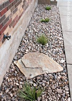Gravel around the foundation for drainage, plant shrubs along to help soak up water. Like the idea of the large rock to prevent erosion from the water spicket. Maybe a few cool pots or barrels with plants too? I like :)                                                                                                                                                                                 More