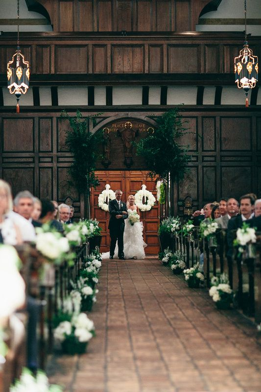 the bride and her father arrive at the rear entry of the chapel. wedding wreaths of white hydrangea hang on the doors, drake elm trees flank the entrance and white flowers and greenery line the aisle.