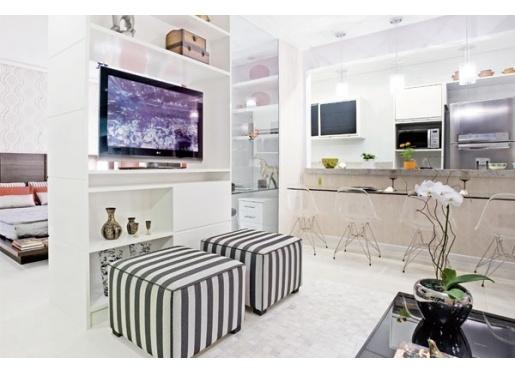 """A estante abriga uma estrutura que permite que a TV rotacione em torno do próprio eixo e atenda aos dois cômodos. """"Para completar essa 'parede', usei um pano de vidro temperado transparente do piso ao teto, obedecendo ao conceito dos ambientes integrados"""", conta Janete."""