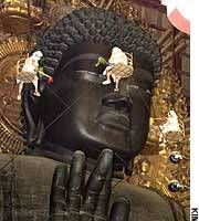 Monks clad in white clean the Big Buddha at Todai-ji Temple in Nara during the annual 'O-minugui (wiping dust off the body)' event on Aug. 7, 2002