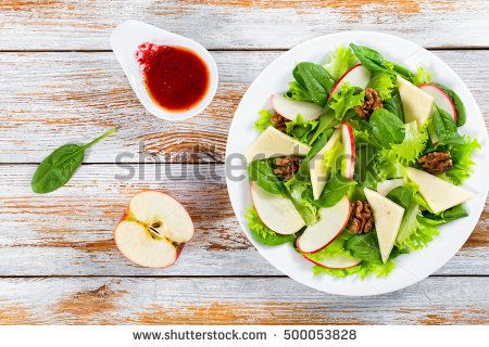 delicious autumn  salad: apple, spinach, cheese slices, lettuce, walnuts, cranberry on white dish  on chopping board with knife and fork, berry dressing on old rustic  planks, close-up
