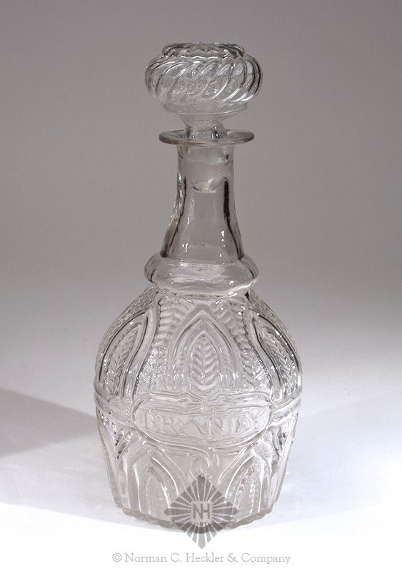 "Blown Three Mold ""Brandy"" Decanter, probably Boston and Sandwich Glass Works, Sandwich, Massachusetts, 1820-1840. Bulbous form, colorless, tooled flared mouth - pontil scar, ht. with stopper 10 3/4 inches; (3/4 inch fissure at pontil scar, light content stain on interior base, top and sides of mouth have been finely ground, shallow 1/8 inch flake from interior mouth edge). GIV-7 Strong mold impression. Beautiful and detailed pattern. Property of The Strong, sold to benefit the museum's…"