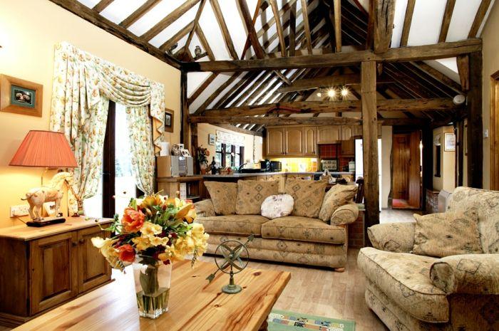 mueble salon, salon rústico, mesa de madera con flores, viga de techo, cortinas florales