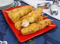 Na foto, o espetinho de frango com cebola empanado está em um prato quadrado de vidro vermelho. Os espetinhos estão bem dourados. Na decoração, a mesa está com uma toalha azul e ao fundo estão pratos empilhados e frascos com tempero.