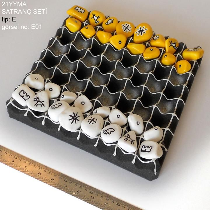 renkli satranç taşları -- Chess set made with painted pebbles and foam egg crate as a board.