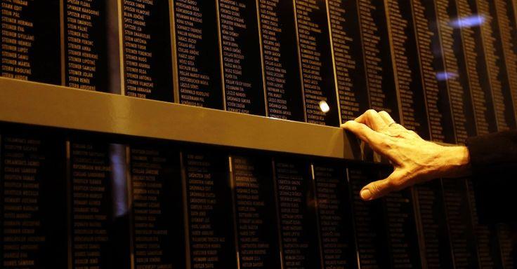 27.jan.2014 - Idoso toca o muro em que estão gravados os nomes das vítimas do regime nazista no Memorial do Holocausto de Budapeste, na Hungria. O dia da libertação do campo de concentração de Auschwitz lembra os seis milhões de judeus mortos no genocídio, sendo que mais de meio milhão eram húngaros