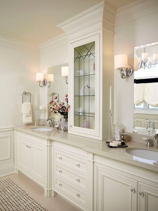 Gorgeous #bathroom with millwork #design, white cabinetry, and decorative #glass door