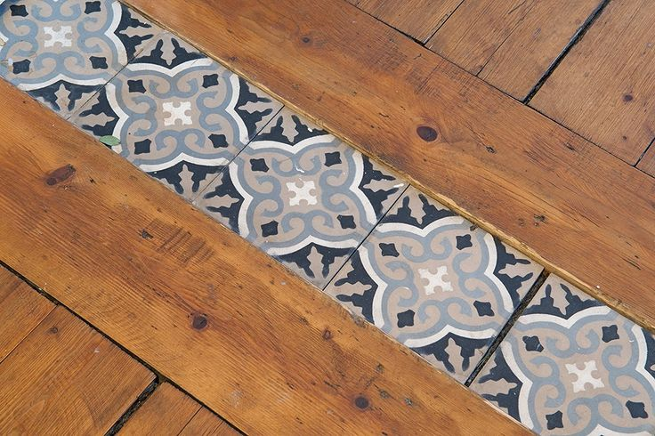 Love this fun tile threshold to transition the wood floors between the kitchen and dining room.  It might be neat if it were the same as the backsplash design over the stove.