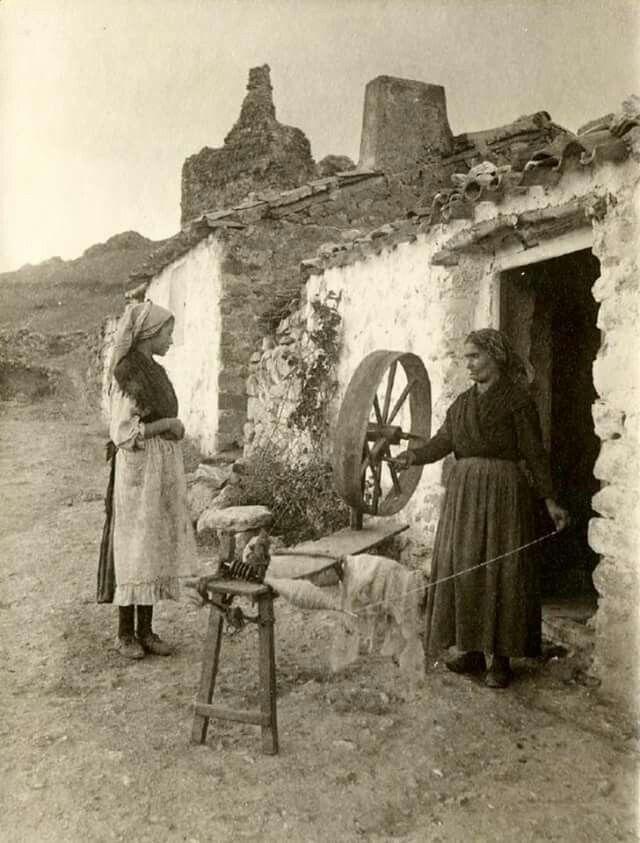 Alcaraz-Albacete.1917.Dos mujeres en la puerta de su casa,una de ellas,hilando con la rueda.Ftf.Pedro Román Martínez. europeana.eu