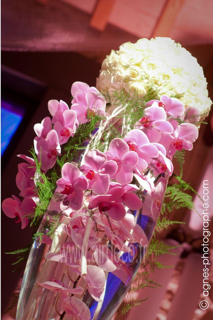 Cette composition florale comprenant un vase rempli d'orchidées roses et surmonté par une boule de roses blanches sera idéale pour votre centre de table.