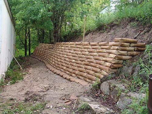 Retaining wall using bags of concrete. After wall is built, soak with water until saturated. Paper will decompose after time. This would be a good alternative for my backyard.