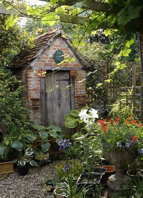 Old brick potting shed with a greenman plaque over the door |  pots of hostas, Agapanthus, and Lilies