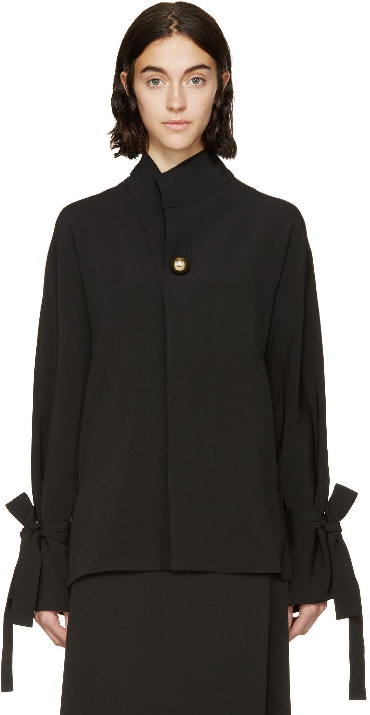 Long sleeve crepe blouse in black. Stand collar. Accent button in pale gold-tone at chest. Concealed button closure at front. Slit at side-seams. Removable and adjustable tie feeds through slits at cuffs. Tonal stitching.