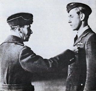 """King George VI confers the DFC to P/O Albert G """"Lew"""" Lewis of No 85 Squadron RAF in an award ceremony at RAF Debden the day after it was gazetted on 25 June 1940 for destroying 5 Me 109 fighters in 2 patrols on 19 May. The recommendation was made by S/L John OW """"Doggie"""" Oliver on watching the 22-year-old South African despatching 3 over Seclin in Hurricane Mk I AK-A, still bearing markings of No 213 Squadron RAF, before evacuating the base for Merville later the day."""