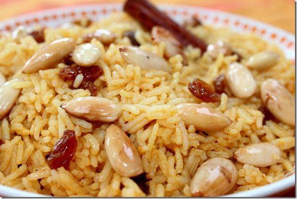 250 g de riz basmati 3cm de bâton de cannelle ¼ de c à c de curcuma en poudre 2cuil.à soupe d'huile ¼ de c à c de concentré de tomates 1cuil.à soupe de raisin secs,sel et poivre noir moulu 25g d'amande grillées, pour le service
