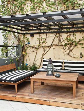 terraza soada en un con prgola de hierro pintada en negro bancos y mesa