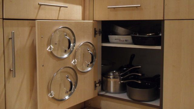Use adhesive hooks to organize your pot lids to the inside of the cabinet door to save space